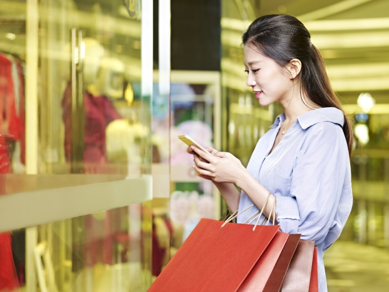 Cinese fa shopping in un centro commerciale con buste rosse in mano e smartphone