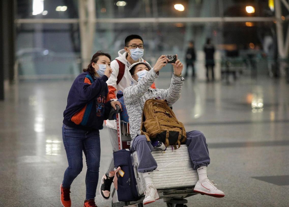 Turisti cinesi con mascherine per corona virus in aereoporto