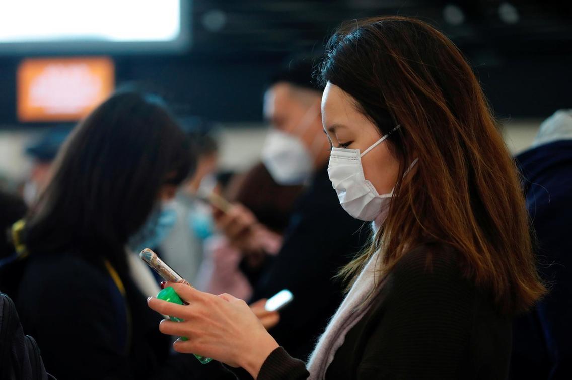 Cinese con mascherina e smartphone in aeroporto