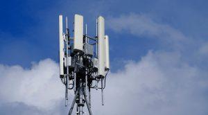 Estremità superiore di un'antenna per la trasmissione di segnale 5G circondata da cielo azzurro e nuvole bianche e grigie