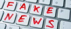 Tastiera da computer con tasti bianchi in cui sono stati disegnate delle lettere in rosso per formare la scritta fake news